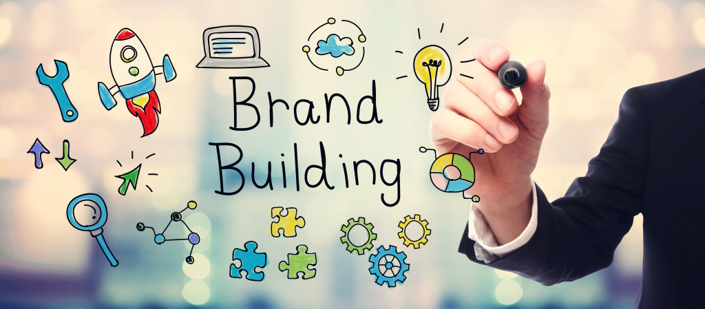 Businessman drawing Brand Building concept on blurred abstract background